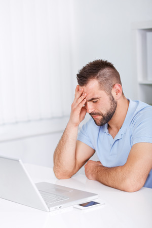 Young business man under stress with headache and migraine photo