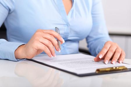 revisando documentos: La mujer joven lee un contrato firmado sobre una mesa blanca