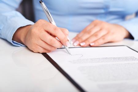 Joven mujer firma un contrato en una mesa blanca Foto de archivo