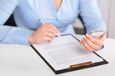 Young woman working with a mobile phone and holding a pen over contract photo