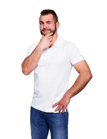 pensive man: Young man thinking in a white polo shirt isolated on white background Stock Photo