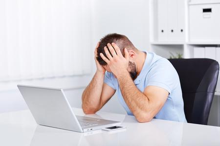 Joven hombre de negocios bajo estrés con dolor de cabeza y migraña Foto de archivo