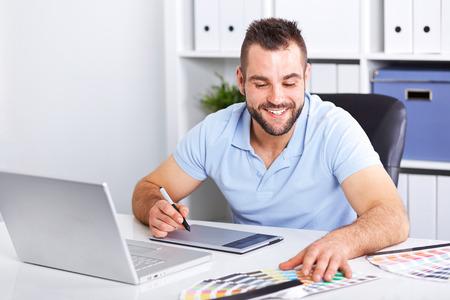 Graphiste heureux � l'aide d'une tablette graphique dans un bureau moderne Banque d'images