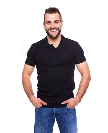 Hombre feliz joven en una camisa de polo negro sobre fondo blanco