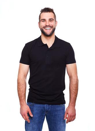흰색 배경에 검은 폴로 셔츠에있는 젊은 행복한 사람