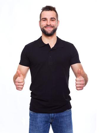 Hombre feliz que da con las dos manos los pulgares sube la muestra sobre el retrato en el fondo blanco