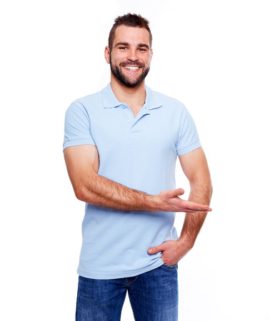 Happy young man in polo shirt showing empty copyspace on white background photo