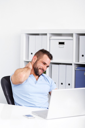 Young businessman has pain of the cervical when working with laptop in office photo