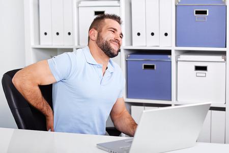 Jonge zakenman heeft rugpijn op het werk met een laptop op kantoor
