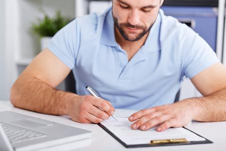 revisando documentos: Hombre de negocios joven en camisa polo azul firma un contrato en blanco de mesa