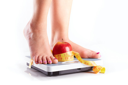 bathroom women: A pair of female feet standing on a bathroom scale with red apple and tape measure between them Stock Photo