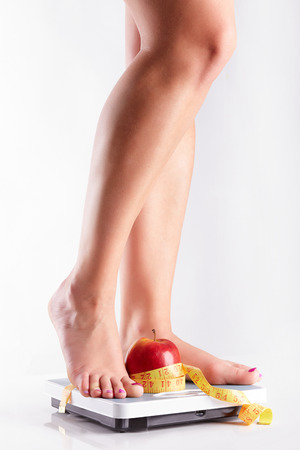 A pair of female feet standing on a bathroom scale with red apple and tape measure between them Stock Photo