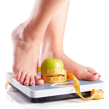 A pair of female feet standing on a bathroom scale with green apple and tape measure between them Stock Photo