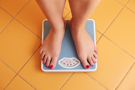 low scale: A pair of female feet standing on a bathroom scale Stock Photo