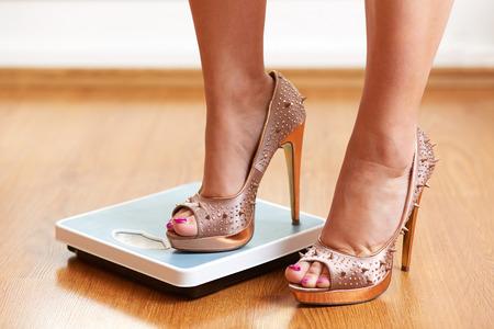 pied fille: Pieds féminins en talons aiguilles d'or avec l'échelle de poids sur le plancher en bois Banque d'images