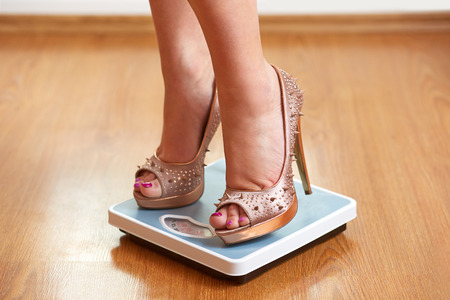 Weight Scale: Female feet in golden stilettos with weight scale on wooden floor