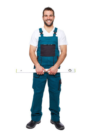 water level: Smiling worker in green uniform with spirit level isolated on white background
