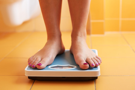 weight control: A pair of female feet standing on a bathroom scale Stock Photo