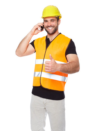 Young engineer in a reflective vest with yellow helmet calling by phone photo