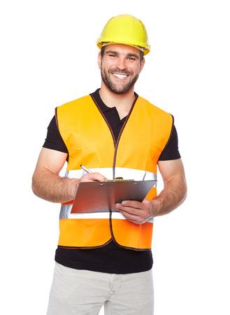 Ingeniero sonriente joven que escribe en una carpeta de negro, sobre fondo blanco