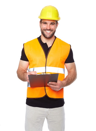 safety vest: Young smiling engineer writes on a black folder, isolated on white background