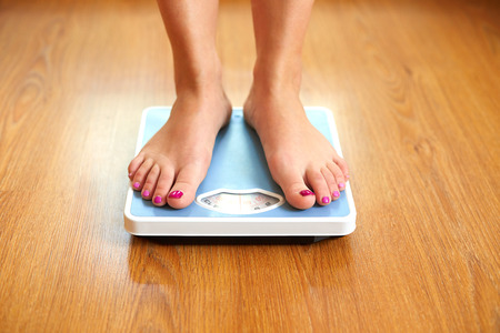 Female bare feet with weight scale on wooden floor photo