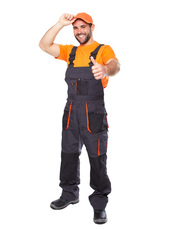 Retrato de la sonrisa trabajador en uniforme azul con las manos haciendo un gesto bien aislado en fondo blanco