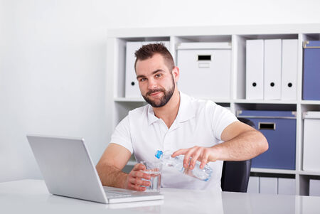 Handsome young man pouring water into a glass from a pet bottle of in the office
