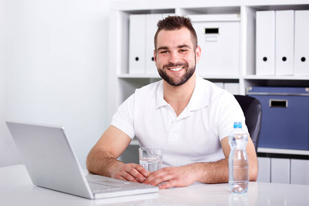 Handsome young man pouring water into a glass from a pet bottle of in the office photo