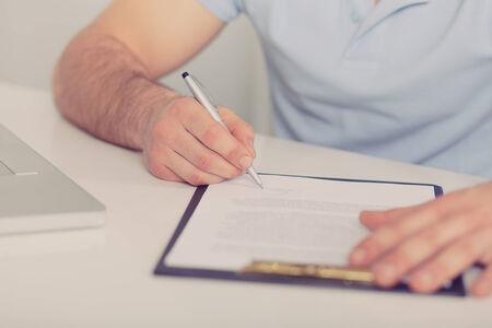 legal document: Hombre de negocios joven en camisa polo azul firma un contrato en el cuadro blanco, tonos Foto de archivo