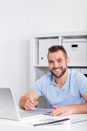 Feliz dise�ador gr�fico utilizando una tableta gr�fica en una oficina moderna