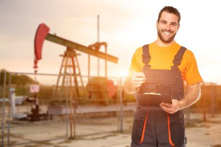bomba de gasolina: Trabajador Refinería lee los datos de las placas de negro, el fondo de la bomba de aceite Foto de archivo