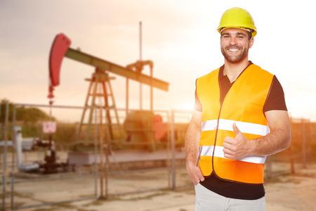 Trabajador de la refinería de pie delante de la bomba de aceite