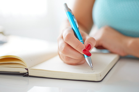 若い女性は白いテーブルに黒い日記を書き込みます
