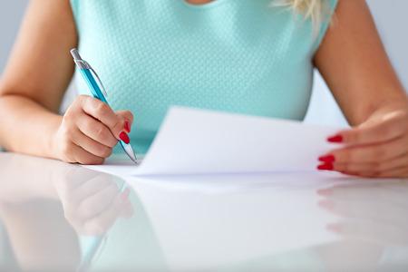 revisando documentos: Joven mujer firma un contrato en una mesa blanca Foto de archivo