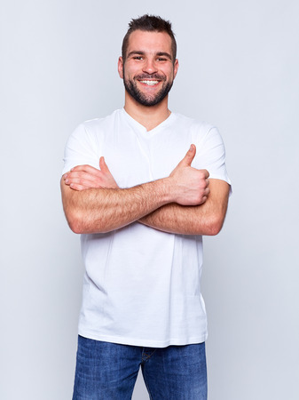 Young handsome man in a white t-shirt on gray background