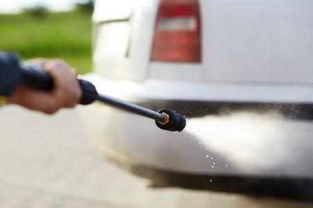 machine à laver: Homme se lavant sa voiture avec l'aide d'un jet d'eau à haute pression Banque d'images