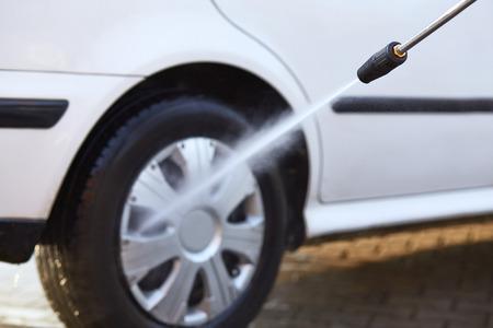 Hombre que lava su coche con el uso de un chorro de agua a alta presi�n Foto de archivo