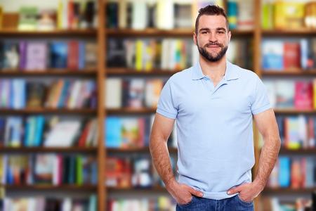 Hombre joven en una camisa polo azul con una librer�a