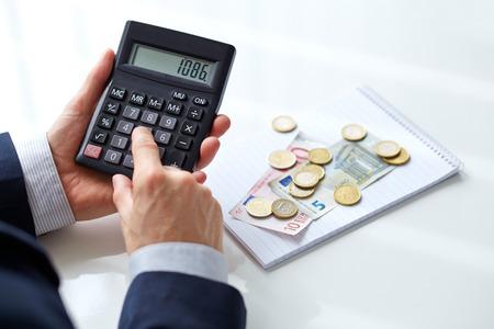 impuestos: Manos masculinas con la calculadora Foto de archivo
