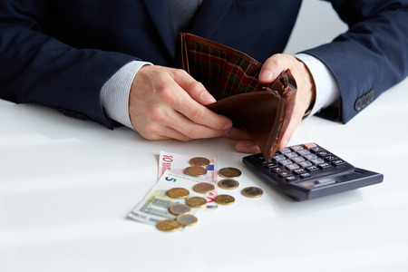 man holding money: Businessman with empty wallet and a few coins on the table Stock Photo