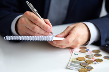 Businessman hand holding a pen writing on notepad with coins   calculator aside photo