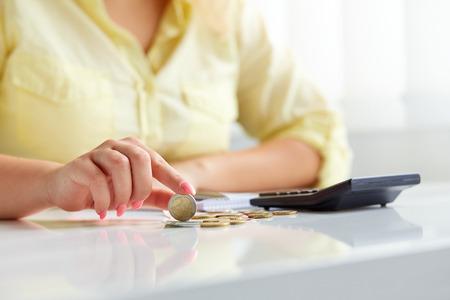dinero euros: Manos femeninas con monedas de euros. Cálculo en la oficina Foto de archivo