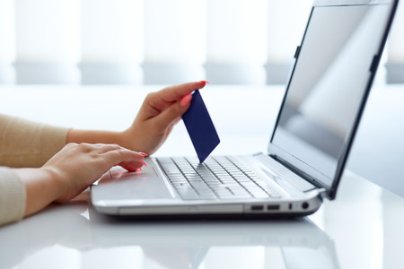 business credit application: Female hand inserts data into the notebook and holding credit card