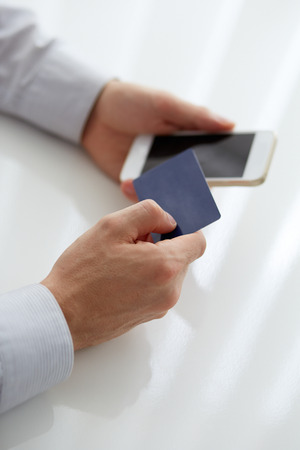 Male hands holding credit card when paying mobile phone photo