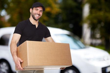 Homem de sorriso entrega segurando uma caixa de papel