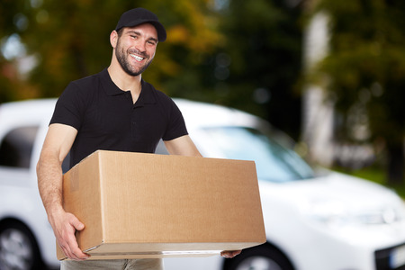 Smiling delivery man holding a paper box Stockfoto