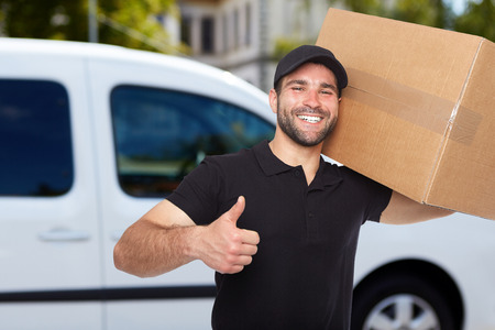 mover: Smiling delivery man holding a paper box Stock Photo