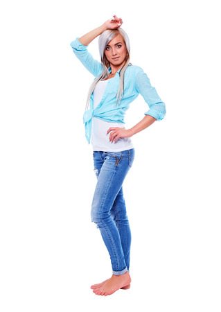 Young woman in a turquoise shirt with bare feet on white background photo