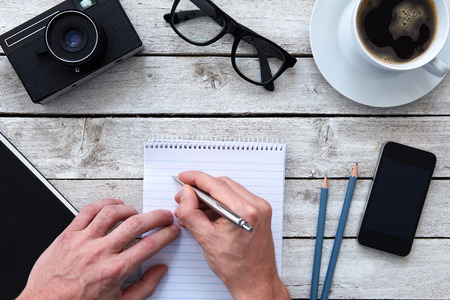 Top view of a hands with pen and coffee on workplace photo